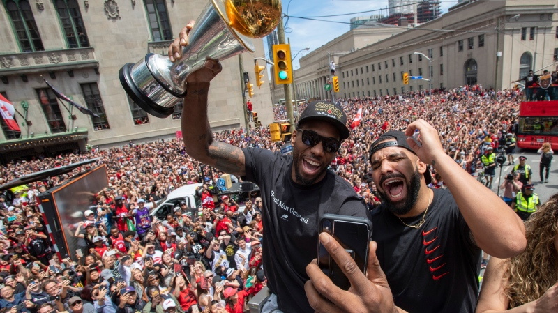 Toronto Raptors' Kawhi Leonard holds his MVP trophy while celebrating with Drake during the 2019 Toronto Raptors Championship parade in Toronto, on Monday, June 17, 2019. (THE CANADIAN PRESS/Frank Gunn)
