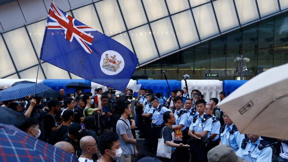 Protesters holding a Hong Kong colonial flag stand off with police officers in Hong Kong on Sunday, July 7, 2019. Protesters in Hong Kong are taking their message to visitors from mainland China on Sunday in a march to a high-speed rail station that connects to Guangdong city and other mainland destinations. (AP Photo/Andy Wong)