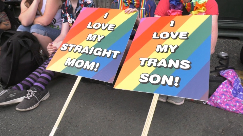 "One of the families celebrating pride this year was that of a 13-year-old transgender man named Morgan, whose mother held a sign saying ""I love my trans son."""