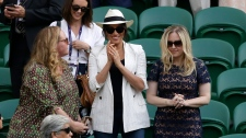 Meghan, Duchess of Sussex, centre, on Court Number One applauds after United States' Serena Williams beat Slovenia's Kaja Juvan in a singles match during day four of the Wimbledon Tennis Championships in London, Thursday, July 4, 2019. (AP Photo/Tim Ireland)