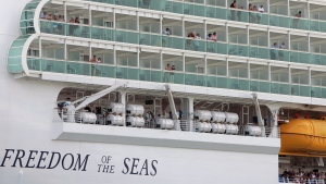 Passengers of the Freedom of the Seas cruise ship, operated by Royal Caribbean Cruises, look out from their stateroom balconies while arriving at the San Juan Port, Puerto Rico, in this 2007 file photo.