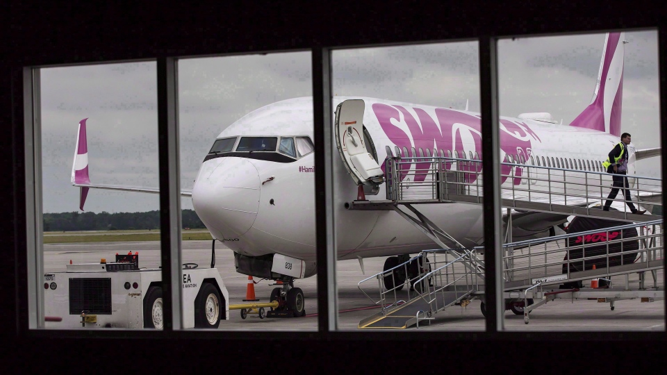 A Swoop Airlines Boeing 737-800 is on display during a media event, June 19, 2018 at John C. Munro International Airport in Hamilton, Ont. (THE CANADIAN PRESS/Tara Walton)