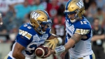 Winnipeg Blue Bombers quarterback Matt Nichols, right, hands the ball to running back Andrew Harris during first quarter CFL action against the Ottawa Redblacks, in Ottawa, Friday, July 5, 2019. (THE CANADIAN PRESS/Adrian Wyld)