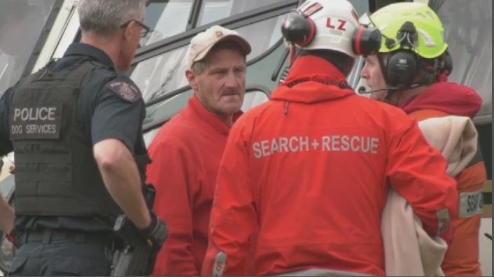 Murray Naswell (second from left) exits a rescue helicopter on Mount Washington on Monday, July 8, 2019. (CTV Vancouver Island)
