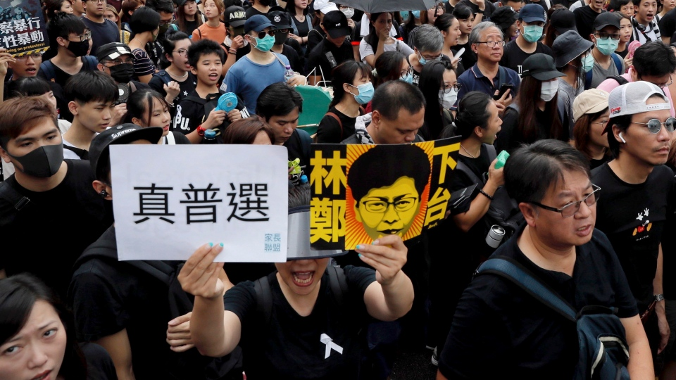 Protesters take part in a march holding a caricature of Hong Kong Chief Executive Carrie Lam with the words 'Step Down' and 'Real election' in Hong Kong on Sunday, July 7, 2019. (AP Photo/Kin Cheung)