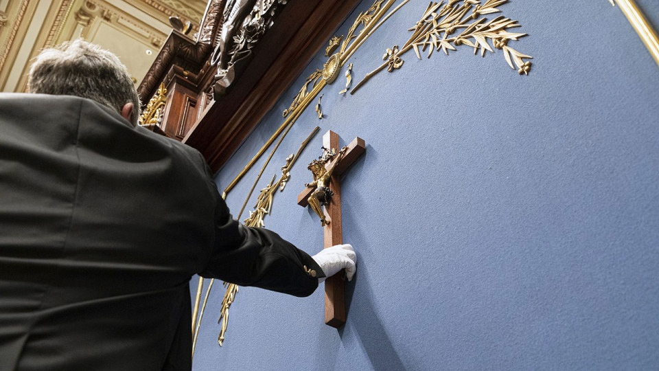 A man removes a crucifix from the wall above the s