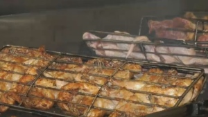 Portuguese chicken cooks on a wood-burning grill