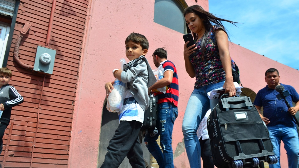 Lucia Ascencio, of Venezuela, carries a suitcase after she and her husband and two sons were returned to Nuevo Laredo, Mexico, as part of the first group of migrants sent back to Mexico's Tamaulipas state under the so-called Remain in Mexico program for U.S. asylum seekers, Tuesday, July 9, 2019. (AP Photo/Salvador Gonzalez)