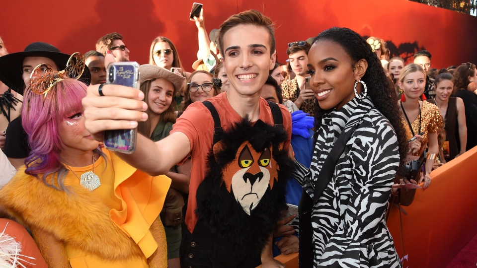 """Kelly Rowland, right, takes a selfie with a fan as she arrives at the world premiere of """"The Lion King"""" on Tuesday, July 9, 2019, at the Dolby Theatre in Los Angeles. (Photo by Chris Pizzello/Invision/AP)"""
