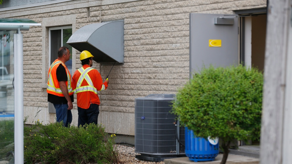 Gas workers check air quality at ventilation vents after emergency personnel were called to a gas leak at a Super 8 hotel in Winnipeg, Tuesday, July 9, 2019. THE CANADIAN PRESS/John Woods