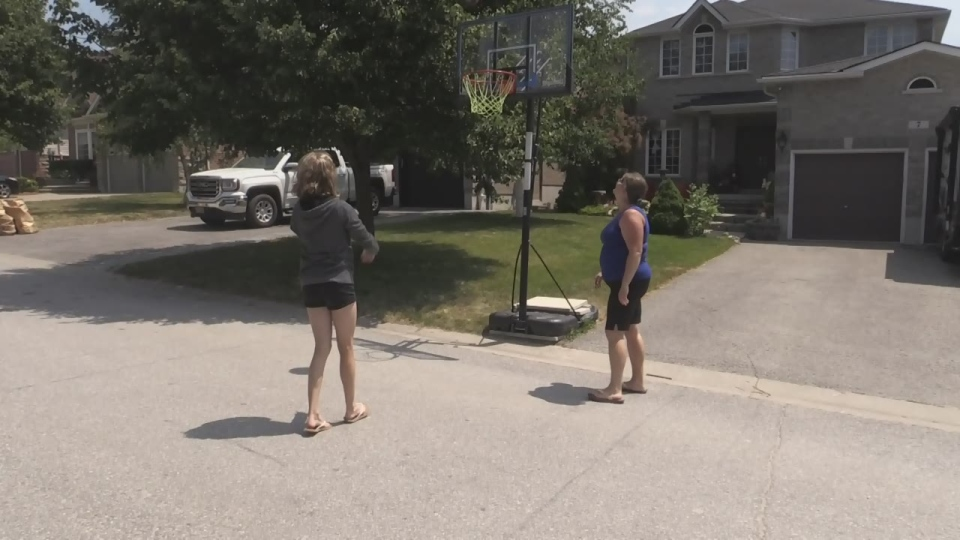 Barrie residents play basketball on the street in Barrie on Wed., July 10, 2019 (CTV News/Aileen Doyle)