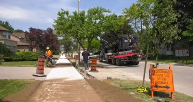 Construction workers replace the sidewalks on Birdsilver Gardens.