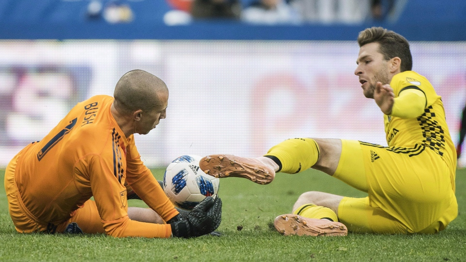 Montreal Impact's goalkeeper Evan Bush makes a save on Columbus Crew SC's Patrick Mullins during second half MLS soccer action in Montreal, Saturday, October 6, 2018. THE CANADIAN PRESS/Graham Hughes