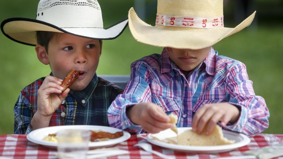 Young cowpokes enjoy a Stampede breakfast in Calgary, Saturday, July 6, 2019. THE CANADIAN PRESS/Jeff McIntosh
