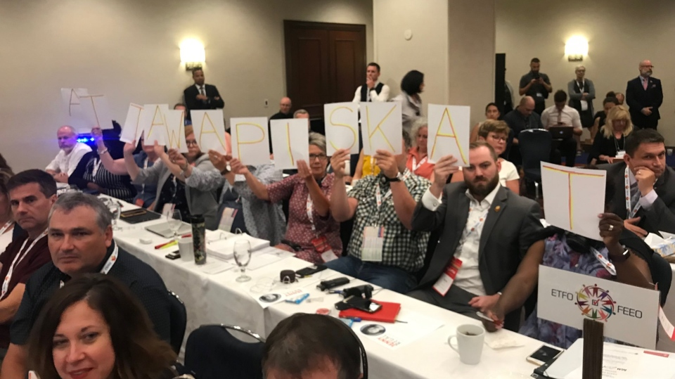 "Protestors silently raise letters spelling ""Attawapiskat"" at the Canadian Teachers' Federation's Annual General Meeting on July 11, 2019. (Glen McGregor/Twitter)"