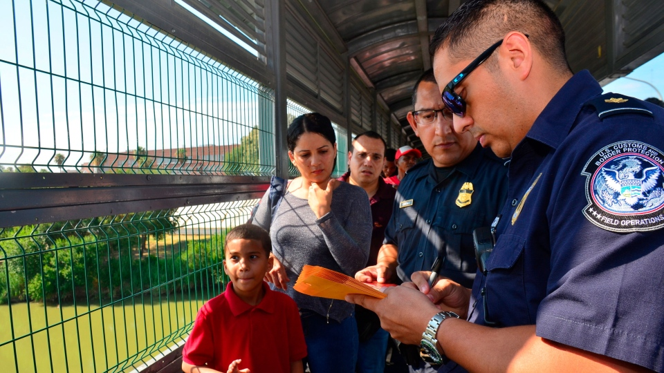 U.S. Customs and Border Patrol agents process a Cuban family, whose turn had been called to cross into the U.S. and apply for asylum, on an international bridge between Nuevo Laredo, Mexico, and Laredo, Texas, Wednesday, July 10, 2019. (AP Photo/Salvador Gonzalez)