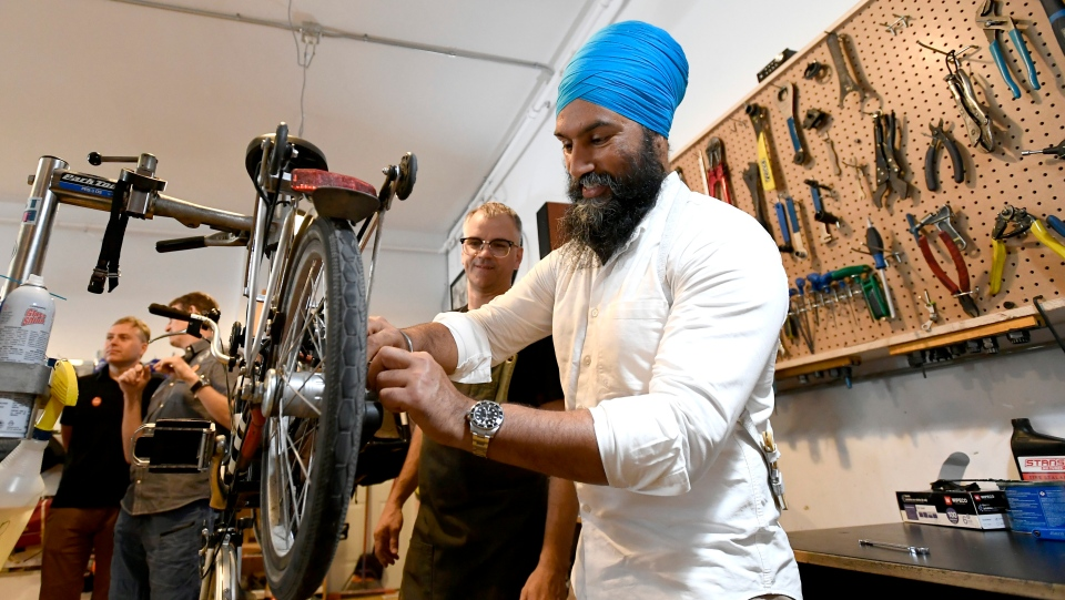 Tall Tree Cycles owner Grant Burke looks on as NDP leader Jagmeet Singh tries his hand at adjusting a Brompton folding bicycle before an announcement for his party's vision for a national cycling strategy at a local bike shop in Ottawa on Thursday, July 11, 2019. THE CANADIAN PRESS/Justin Tang