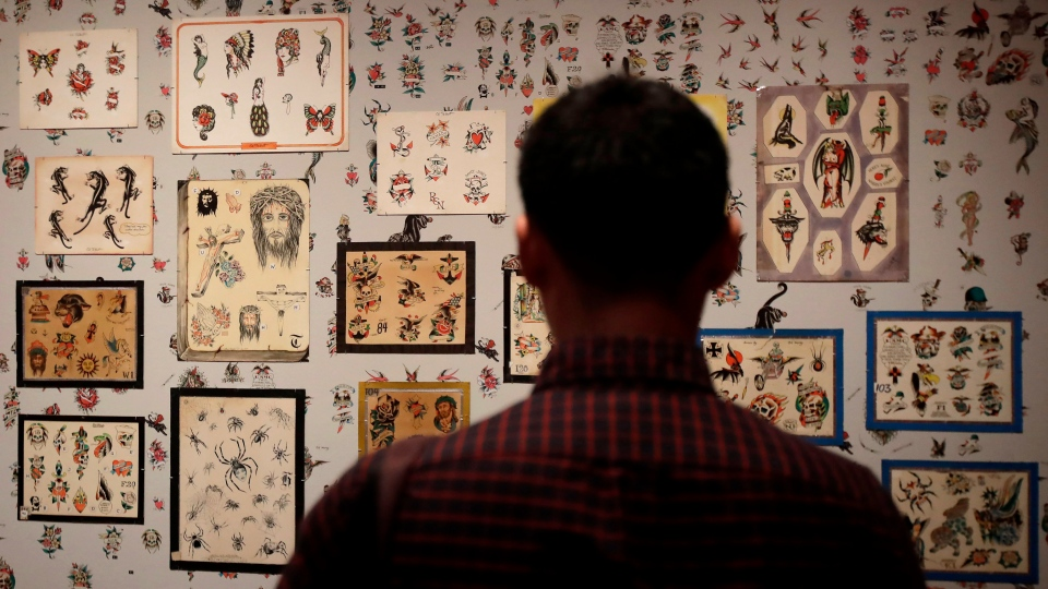 """In this Wednesday, July 10, 2019 photo, a man looks at a wall of tattoos during a media preview of """"Ed Hardy: Deeper than Skin"""" at the de Young Museum in San Francisco. (AP Photo/Jeff Chiu)"""