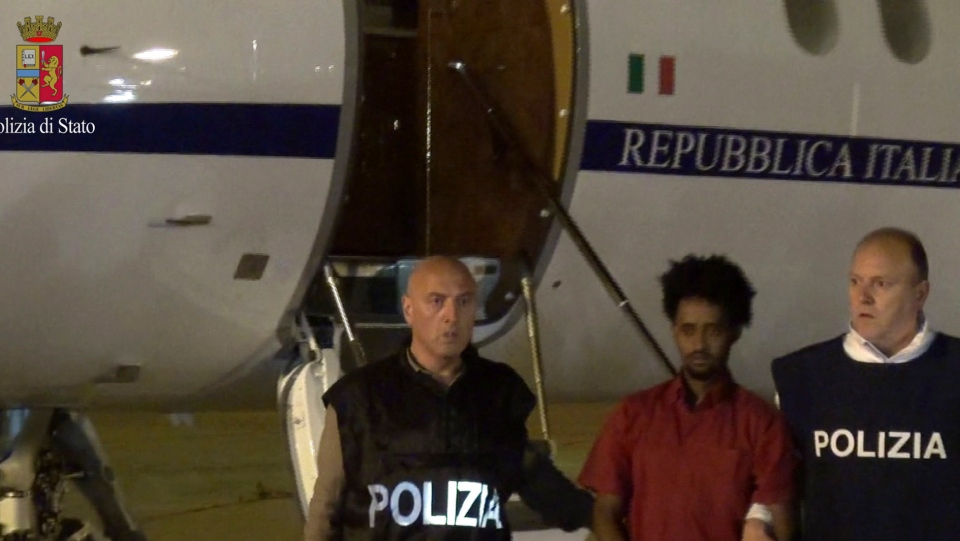 This June 7, 2016 file photo taken from a video and released by the Italian Police shows a man identified then by prosecutors as Medhane Yehdego Mered, center, a 35-year-old Eritrean, arrested two weeks earlier in Sudan, upon his arrival at Ciampino's airport, on the outskirts of Rome. A court in Palermo, Sicily, ruled on Friday, July 12, 2019 that the wrong Eritrean man, Medhanie Tesfamariam Behre, was arrested and ordered his release. ( Italian Police via AP/files)