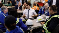Prime Minister Justin Trudeau speaks with workers at the Trans Mountain Terminal in Edmonton on Friday, July 12, 2019. THE CANADIAN PRESS/Jason Franson