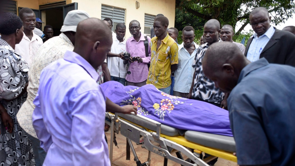 In this file photo, relatives and other mourners watch as the body of South Sudanese journalist Peter Julius Moi is taken into the mortuary in Juba, South Sudan Thursday, Aug. 20, 2015. (AP Photo/Jason Patinkin)