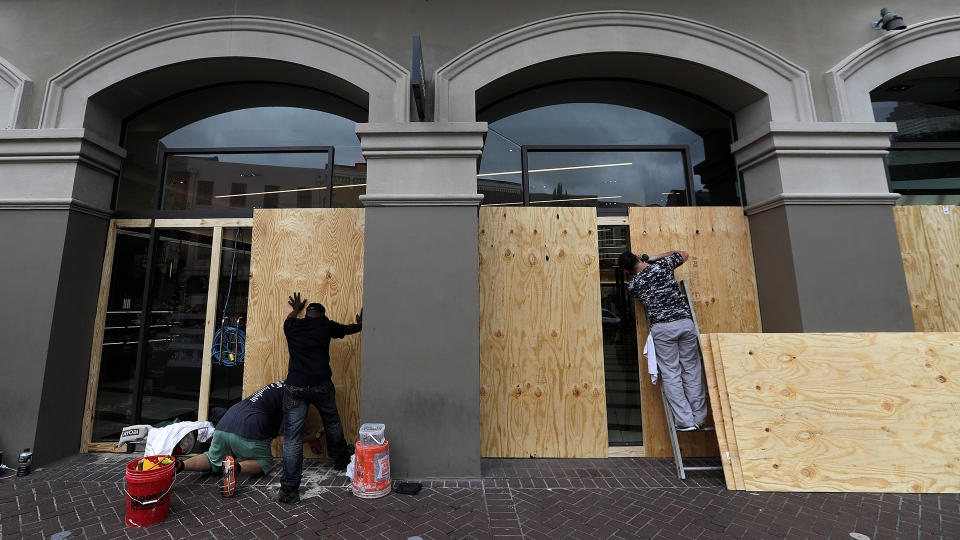 Workers board up windows in the French Quarter Friday, July 12, 2019, in New Orleans, ahead of Tropical Storm Barry. (AP / David J. Phillip)