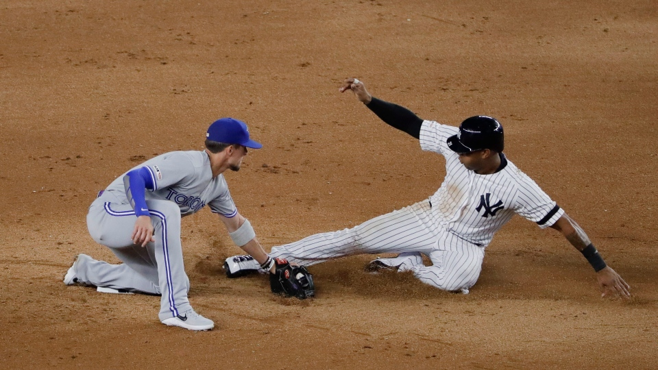 Toronto Blue Jays second baseman Cavan Biggio, left, tags out New York Yankees' Aaron Hicks, right, during the seventh inning of a baseball game Friday, July 12, 2019, in New York. (AP Photo/Frank Franklin II)