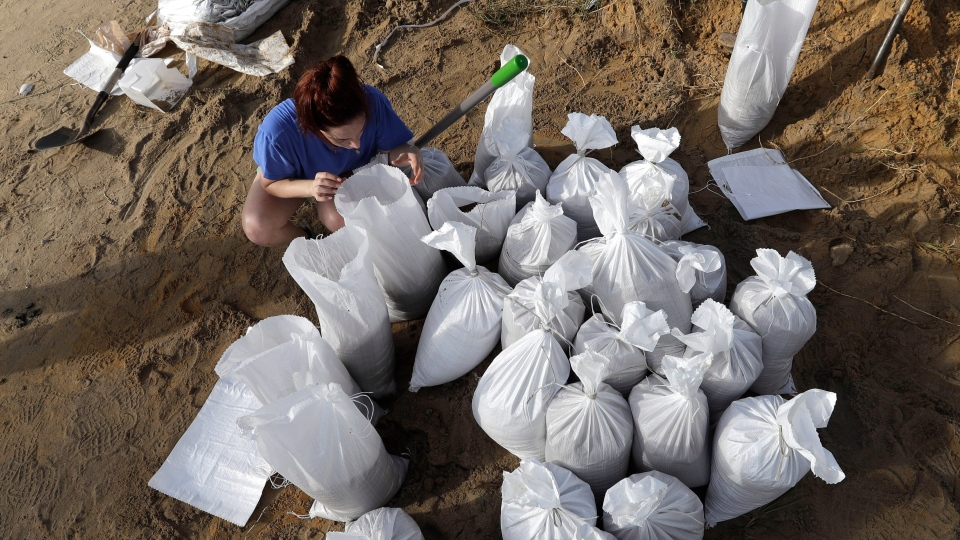 Ashley Boudreaux ties sandbags Friday, July 12, 2019, in Baton Rouge, La., ahead of Tropical Storm Barry. Barry could harm the Gulf Coast environment in a number of ways. But scientists say it's hard to predict how severe the damage will be. (AP Photo/David J. Phillip)