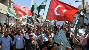 FILE - This September 14, 2018 file photo, protesters wave revolutionary Syrian and Turkish flags as they attend a demonstration against the Syrian government offensive in Idlib, in Maarat al-Numan, south of Idlib, Syria. (Ugur Can/DHA via AP, File)