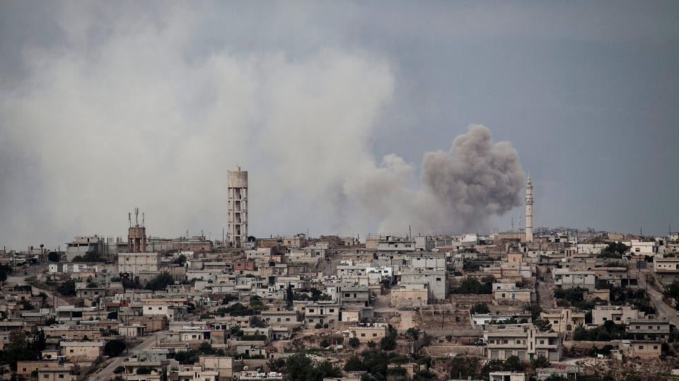 FILE - In this Sept. 19, 2013, file photo, smoke rises after a TNT bomb was thrown from a helicopter, hitting a rebel position during heavy fighting between troops loyal to president Bashar Assad and opposition fighters, in a neighbouring village to Kafr Nabuda, in the Idlib province countryside, Syria. (AP Photo/File)
