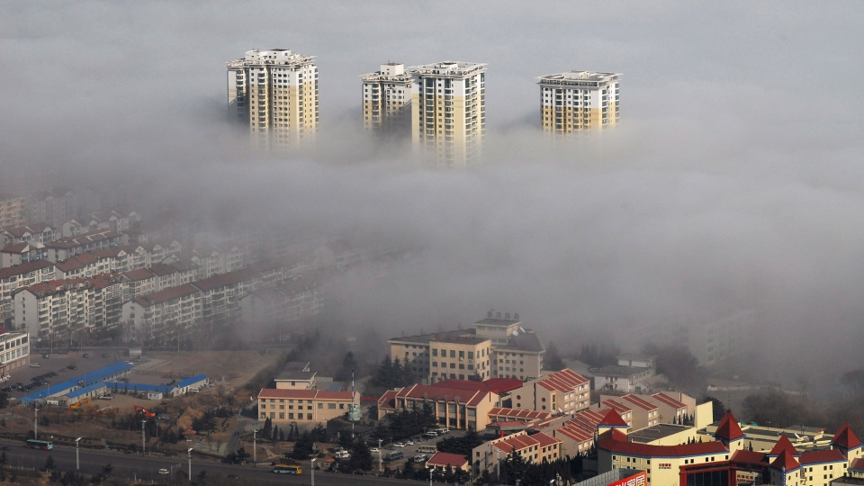 This Xinhua news agency photo taken on Wednesday February 11, 2009 shows fog-wrapped buildings in Yantai city, in east China's Shandong province. (AP Photo/Xinhua, Chu Yang)