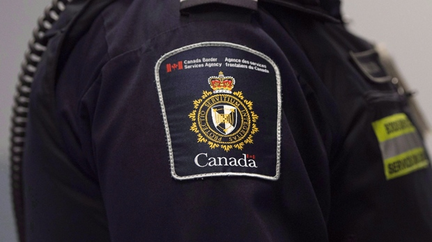 """A Canadian Border Services agent stands watch at Pearson International Airport in Toronto on Tuesday, December 8, 2015. The Canada Border Services Agency will soon force all border security officers working with detained migrants to wear defensive gear, including batons, pepper spray and bulletproof vests, a policy that's drawing widespread concern over a perceived """"criminalization"""" of asylum seekers. THE CANADIAN PRESS/Darren Calabrese"""