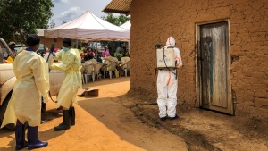 A worker from the World Health Organization (WHO) decontaminates the doorway of a house on a plot where two cases of Ebola were found, in the village of Mabalako, in eastern Congo Monday, June 17, 2019. (AP Photo/Al-hadji Kudra Maliro)