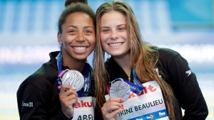 Jennifer Abel and Melissa Citrini Beaulieu of Canada hold their silver medals after competing in the finals of the women's 3 meter springboard synchronized diving competition at the World Swimming Championships in Gwangju, South Korea, Monday, July 15, 2019. (AP Photo/Mark Schiefelbein)