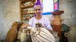 Moroccan potter Aicha Tabiz, also known as Mama Aicha, holds one of her works near the village of Ourtzagh in the foothills of the Rif mountains. (FADEL SENNA / AFP)