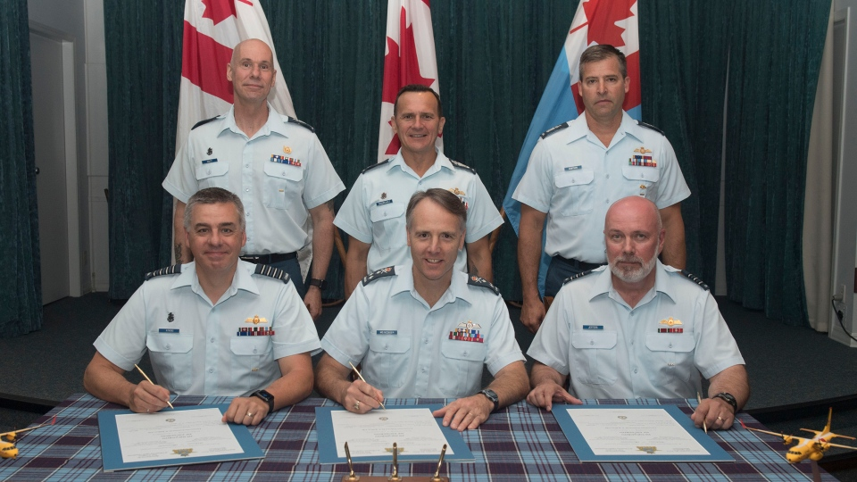 The ceremony appointing Lieutenant-Cololenl Derek Jeffers as commanding officer of the newly reformed 418 Squadron in Comox on July 11, 2019. From left: Colonel Mike Atkins, commander of 19 Wing (who was promoted to the rank of brigadier-general later that day); Lieutenant-General Al Meinzinger, commander of the RCAF; and Lieutenant-Colonel Derek Jeffers co-sign the appointment documents. . Standing behind them are (from left) Chief Warrant Officer Kevin Colcy, 19 Wing chief warrant officer, Chief Warrant Officer Denis Gaudreault, RCAF command chief warrant officer; and Chief Warrant Officer Wayde Simpson, squadron chief warrant officer. (Corporal Nathan Spence/RCAF)