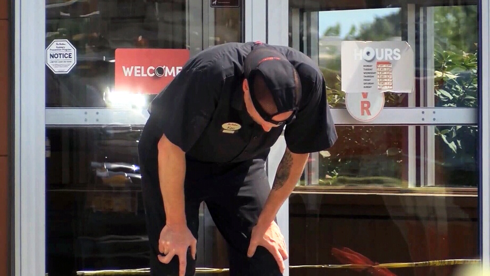 A Tim Hortons employee appears distraught outside the fast food restaurant in Rochester, N.Y. (CNN)