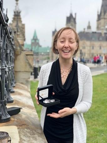 Alisha Giroux holds her Canada-shaped coin. (Daniela Chavez Ackermann)