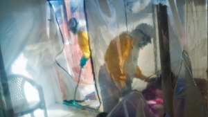 In this photograph taken Saturday 13 July 2019, health workers wearing protective suits tend to to an Ebola victim kept in an isolation cube in Beni, Congo DRC.  (AP Photo/Jerome Delay)