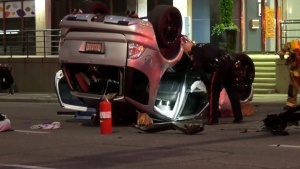 A CPS member surveys the damage to an overturned SUV following a Monday night crash in the downtown core