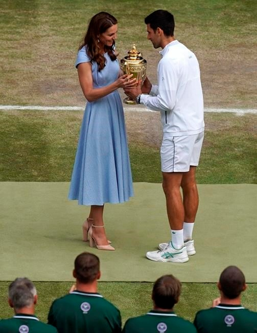 Serbia's Novak Djokovic is presented with the winners trophy by Britain's Kate, Duchess of Cambridge after defeating Switzerland's Roger Federer during the men's singles final match of the Wimbledon Tennis Championships in London, Sunday, July 14, 2019. (Will Oliver/Pool Photo via AP)