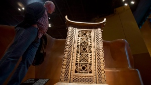 A visitor looks at the wooden and metal throne of the King Ghezo of the Dahomey kingdom, dated 19th century, today's Benin at Quai Branly museum in Paris, France, Friday, Nov. 23, 2018. (AP Photo/Michel Euler)