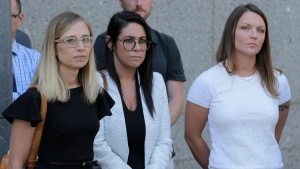 Annie Farmer, left, and Courtney Wild, right, accusers of Jeffery Epstein, stand outside the courthouse in New York, Monday, July 15, 2019. (AP Photo/Seth Wenig)