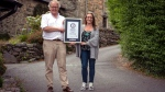 In this undated handout photo provided by Guinness World Records on Tuesday, July 16, 2019, Gwyn Headley and Sarah Badhan, stand on Ffordd Pen Llech with a certificate from Guinness World Records, confirming that the road is the steepest street in the world, in the seaside town of Harlech, North Wales (Andrew Davies/Guinness World Records via AP)