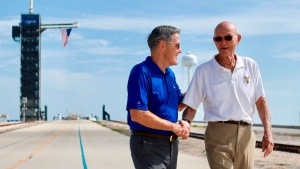 In this photo made available by NASA, astronaut Michael Collins, right, speaks to Kennedy Space Center Director Bob Cabana at Launch Complex 39A, Tuesday, July 16, 2019. (Frank Michaux/NASA via AP)