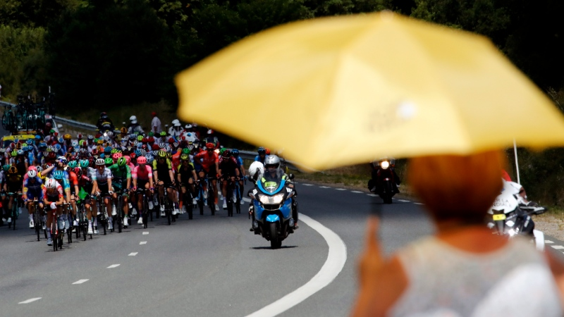 A spectator holds an umbrella along the road as the pack rides during the tenth stage of the Tour de France cycling race over 217 kilometers (135 miles) with start in Saint-Flour and finish in Albi, France, Monday, July 15, 2019. (AP Photo/ Christophe Ena)
