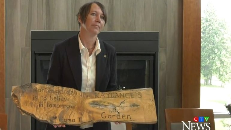 Tasha Brown holds up a sign she made for the garden planted for her daughter Kaydance, who was allegedly abducted by her other mother Lauren Etchells in 2016. July 16, 2019. (CTV Vancouver Island)