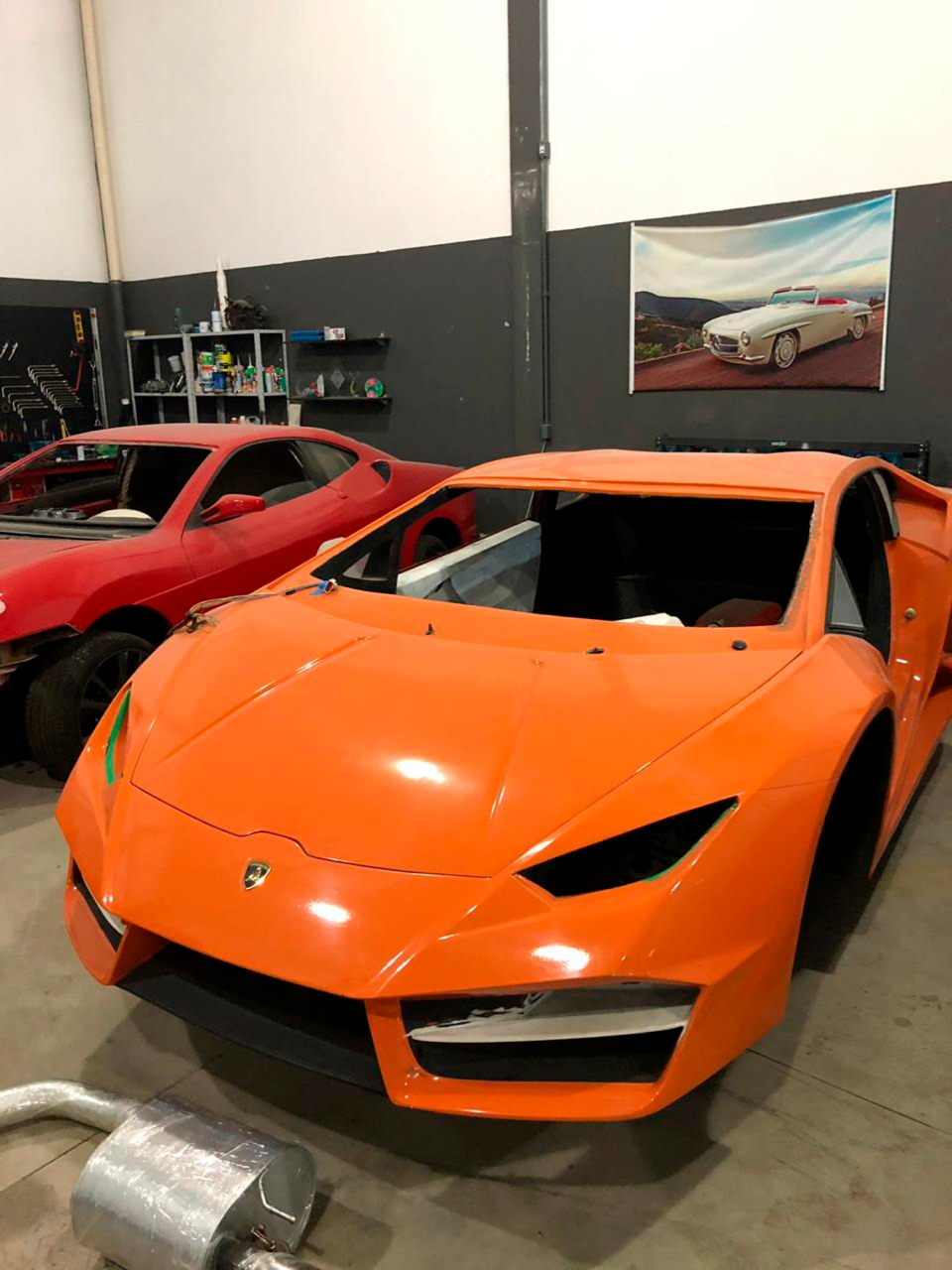 This July 15, 2019 photo released by Itajai Civil Police shows luxury car replicas inside a workshop in Itajai, Brazil. (Itajai Civil Police via AP)
