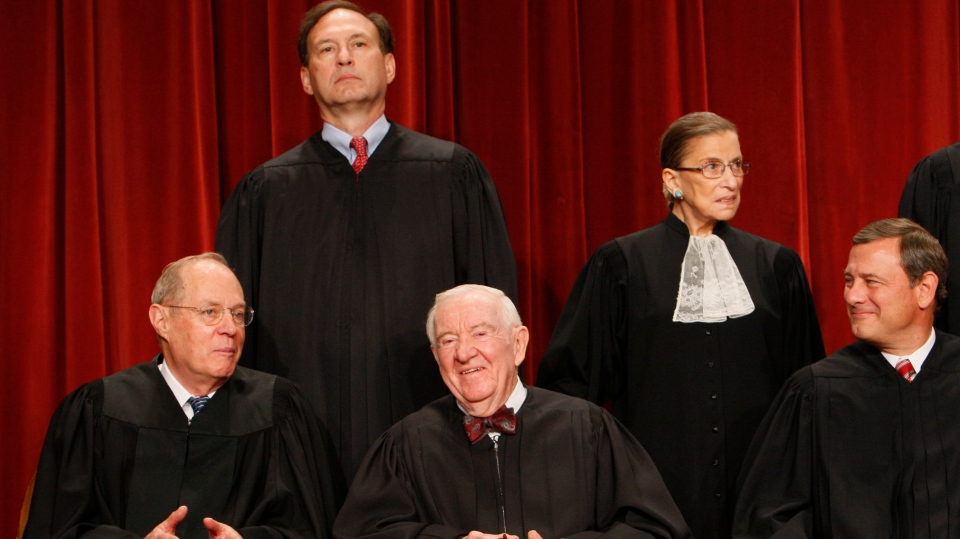 In this Sept. 29, 2009 file photo Associate Justice John Paul Stevens, center, sits for a group photograph at the Supreme Court in Washington.  (AP Photo/Charles Dharapak, File)