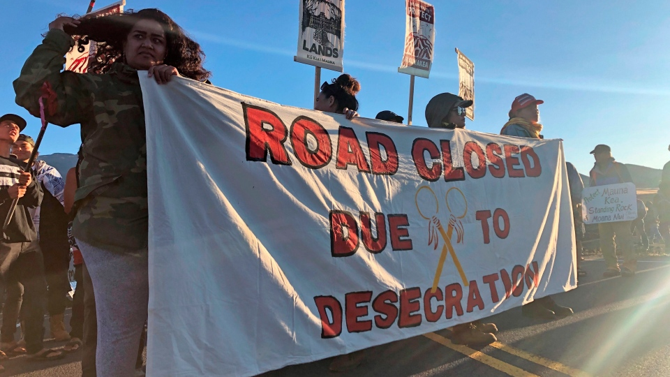 Demonstrators gather to block a road at the base of Hawaii's tallest mountain, Monday, July 15, 2019, in Mauna Kea, Hawaii, to protest the construction of a giant telescope on land that some Native Hawaiians consider sacred. On Wednesday, the Union of B.C. Indian Chiefs said that Canada should remove its financial support for the plan to build the massive new telescope. (AP Photo/Caleb Jones)